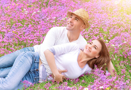 Happy couple spending time outdoors, lying down and hugging on beautiful pink floral field, romantic relationship, love concept photo