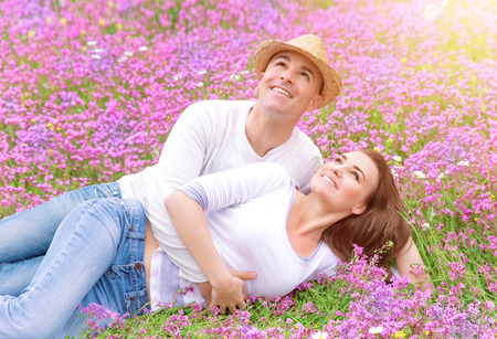 relationship love: Happy couple spending time outdoors, lying down and hugging on beautiful pink floral field, romantic relationship, love concept