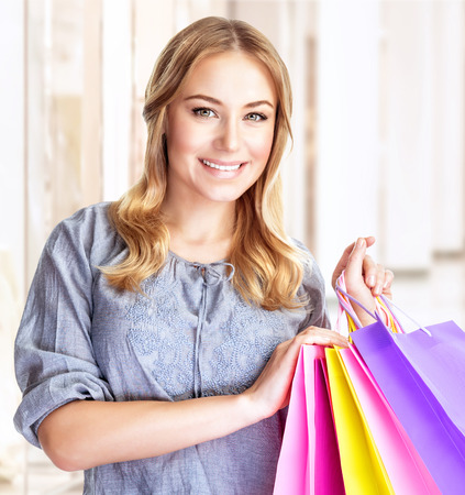 Closeup portrait of happy customer with colourful paper bag in great mall, attractive girl enjoying shopping, buying gifts, spending money concept photo