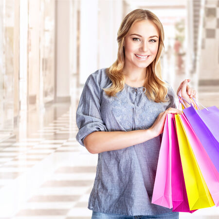 Happy customer with colourful paper bag in great mall, attractive girl enjoying shopping, buying gifts, spending money concept photo