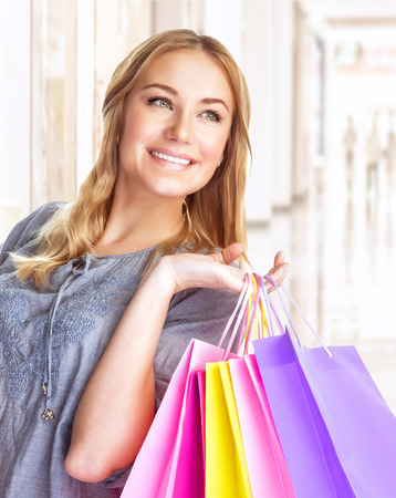 Closeup portrait of sweet cheerful girl standing in big shopping centre with colourful paper bags, doing purchase with pleasure photo