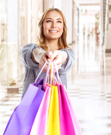 Happy girl with colorful shopping bag, cheerful young female doing purchase in great luxury retail store, spending money with pleasure concept photo