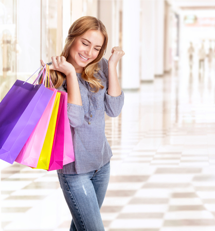 Woman having fun in shopping centre, smiling girl with closed eyes holding in hands colorful paper bags, spending money concept