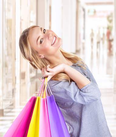 Portrait of happy girl with colourful shopping bag, cheerful young female doing purchase in great luxury retail store, spending money with pleasure concept photo