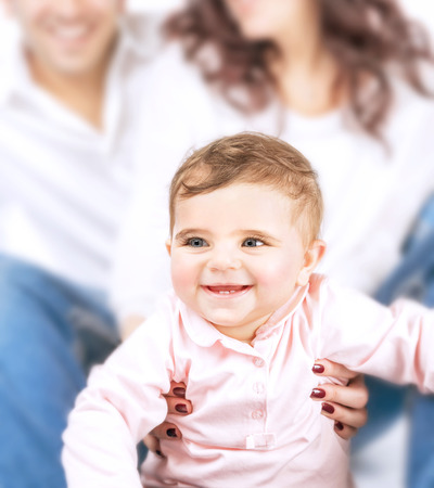 Closeup portrait of little smiling child and soft focus of parents, joyful family, happy parenthood, love and happiness concept  photo