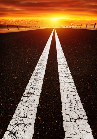 Long highway, road on sunset, red dramatic cloudy sky, two white line on dark asphalt, speed highway along desert,  freedom and travel concept photo