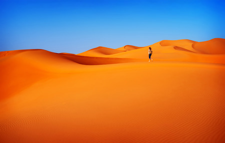 Woman walking in desert, active lifestyle, summertime adventure, expedition in the dunes , hiking trip in sahara, travel and vacation concept photo
