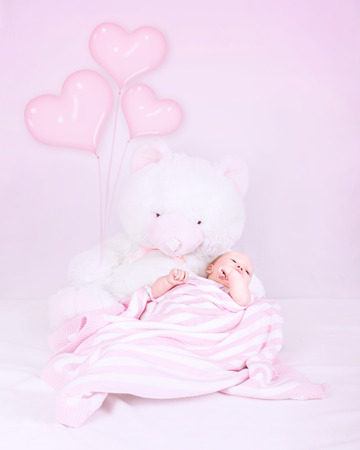 Little baby in bedroom, lying down on big soft toy bear, covered with pink blanket, heart-shape balloons decoration, love and happy childhood concept photo