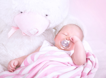 Cute newborn baby sleeping with pacifier in mouth, lying down on big white soft toy teddy bear, peaceful nap, happy childhood concept photo