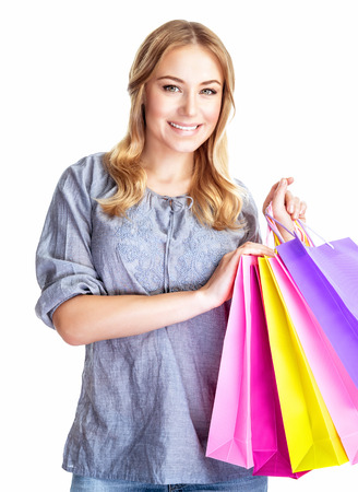 spending money: Happy shopper girl with four colourful paper bags isolated on white background, doing purchase, sale and spending money conception