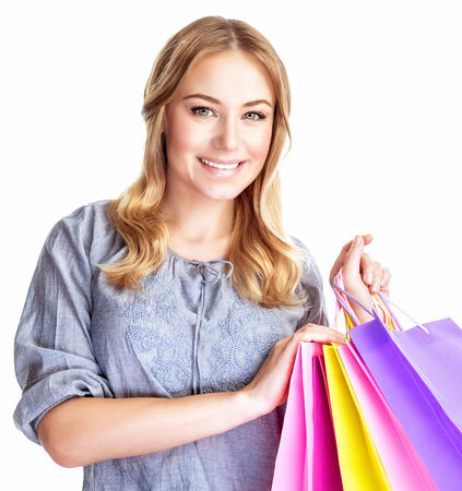 Closeup portrait of happy shopper girl with four colourful paper bags isolated on white background, doing purchase, sale and spending money conception photo