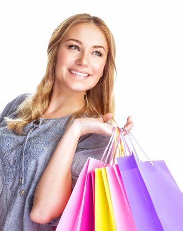 Closeup portrait of cute blond girl holding in hands paper bags isolated on white background, enjoying shopping, happy consumer concept photo