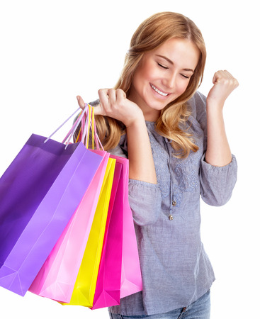 Happy shopper girl closed her eyes with pleasure and holding in hand colorful shopping bags, isolated on white background photo