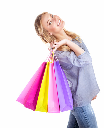 Excited shopper, cheerful girl holding in hand colorful gift bags isolated on white background, hobby of spending money, sales concept photo