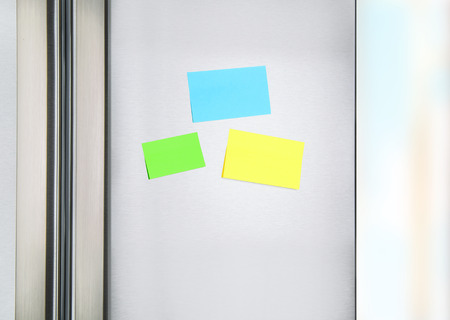 Sticky notes on the fridge, three colorful paper on the door on refrigerator for message, little reminder sheets, communication on the kitchen photo