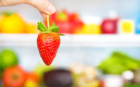 Eating healthy food conceptual background, weight loss and body care concept, fresh strawberry in hands, full fridge of diet nutrition, selective focus photo
