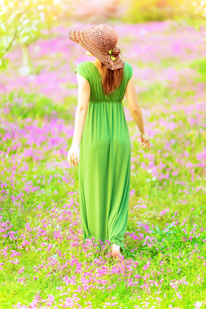 Sensual woman walking in spring garden, rear view, beautiful fresh floral field, sunny day, gentle fashion style, freshness and tenderness of nature concept