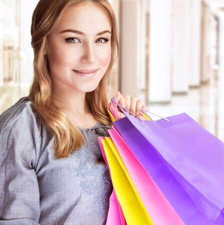 Closeup portrait of beautiful happy woman doing purchase in shopping center, carrying colorful paper bags, spending money concept photo