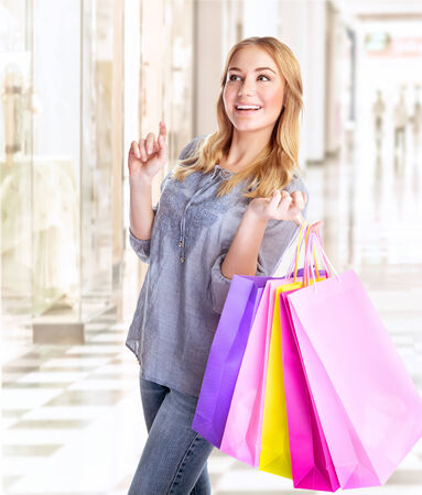 Happy female with shopping bags in retail store, enjoying purchase in the mall, excited consumer with colorful paper bags, conception of pleasure photo