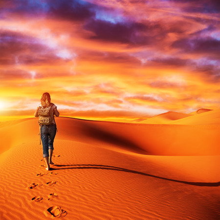 Traveller in the desert, active young woman trekking in hot sandy wilderness, dramatic sunset, summertime adventure, extreme tourism concept photo