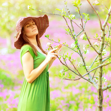 Closeup portrait of beautiful sensual forest nymph touch blooming tree twigs with closed eyes, dreamy photo, fairy tale, spring season Stock Photo