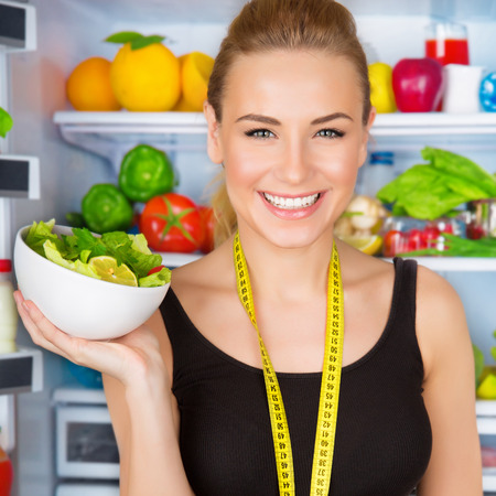 dietitian: Closeup portrait of beautiful cheerful girl holding in hand bowl with fresh tasty green salad, dietitian recommending eating vegetables, healthy organic nutrition concept