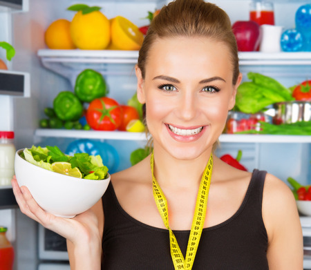 Closeup portrait of cute smiling woman with measure tape and fresh vegetables salad, sportive trainer, organic food, health and beauty care concept  photo