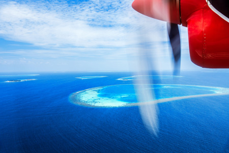 Luxury holidays, flight to resort on a little red water airplane, flight over beautiful blue sea, aerial scenic view, traveling and tourism concept photo
