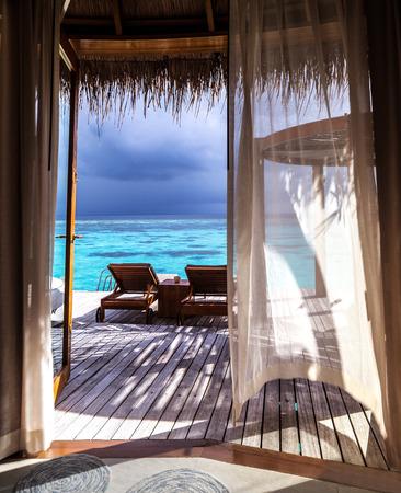 豪華なロマンチックな新婚旅行、水、テラスでは、モルディブでは、夏の時間概念の休暇の 2 つのデッキチェアの上の美しい木製バンガローの配置