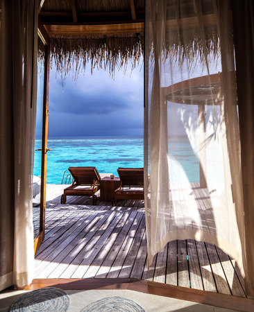 Luxury romantic place for honeymoon, beautiful wooden bungalow on the water, two deckchair on the terrace, vacation on Maldives, summer time concept  photo