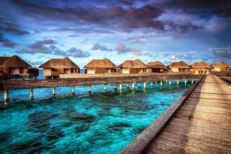 Resort de lujo, muchos bonito bungalow sobre el agua, vistas increíbles, hermoso coral bajo el agua transparente, las vacaciones de verano concepto Editorial