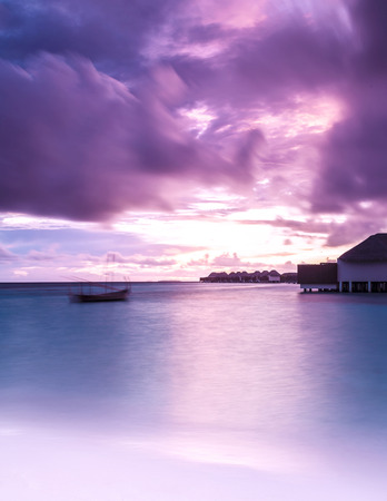 Luxury resort, dramatic purple sunset on the ocean, cloudy sky, summer vacation, little beach house on the seashore
