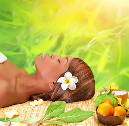 Beautiful young african woman enjoying day spa, lying down on massage table with closed eyes, take medical treatment outdoors, luxury spa resort photo