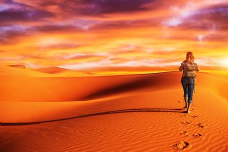 アクティブな女性砂漠に沿ってトレッキング、砂丘で単独で歩いて、自然、荒野、旅行および観光事業の概念への遠征を発見