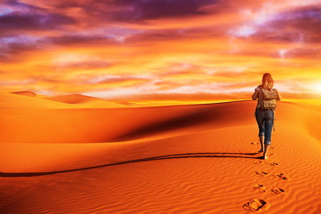 discovering: Active woman trekking along desert, walking alone in the dune, discovering nature, expedition to the wilderness, travel and tourism concept