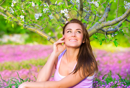 Portrait of happy woman in blooming garden, having fun outdoors, sitting down on pink floral meadow, spring time concept photo