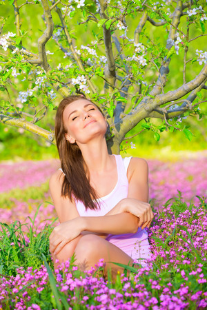 Portrait of beautiful calm girl with closed eyes sitting down on pink floral glade under blooming apple tree, relaxation outdoors in spring time photo