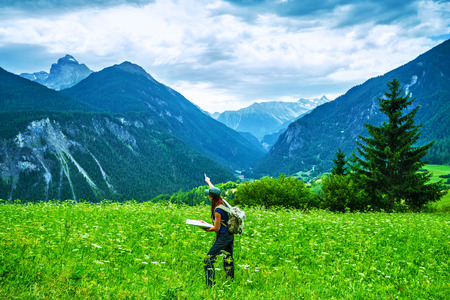 european alps: Happy traveler in the mountains, active woman searching right way on the map, travel to Alpine mountain, journey and adventure concept Stock Photo
