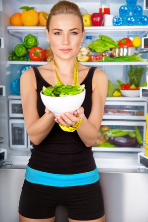Healthy woman with fresh salad standing near open fridge full of vegetables, athletic girl with measure tape, perfect body, organic food concept  Stock Photo