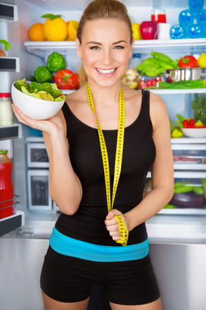 dietitian: Healthy woman with fresh salad standing near open fridge full of vegetables, athletic girl with measure tape, perfect body, organic food concept  Stock Photo