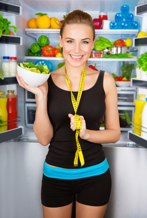 fridge: Portrait of beautiful cheerful girl holding in hand bowl with fresh tasty green salad, dietitian recommending eating vegetables, healthy organic nutrition concept Stock Photo