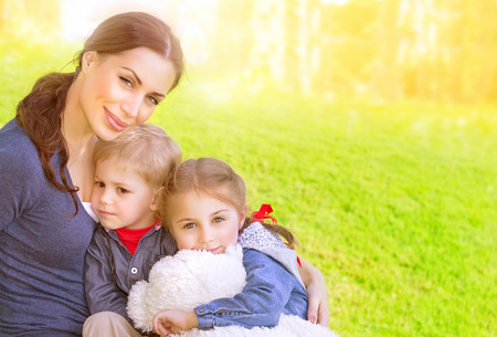 Portrait of beautiful young mother with cute daughter and son sitting on the meadow, sunny day, love and happy family concept photo