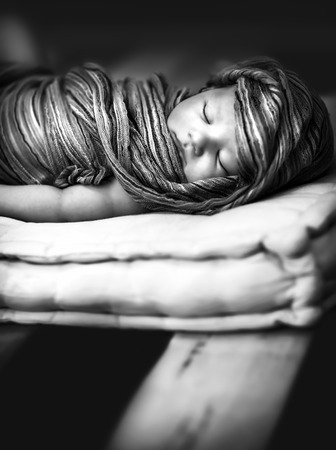 Closeup black and white photo of cute sleeping baby wrapping in stylish scarf, peaceful nap, innocence concept photo