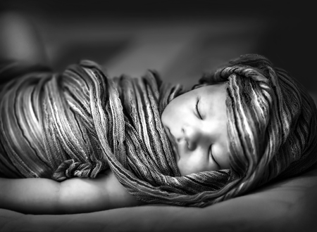 Closeup portrait of adorable newborn girl sleeping at home, black and white photo of little baby wrapped in fashionable shawl  photo