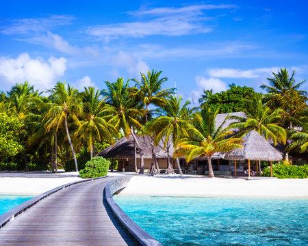 island paradise: Luxury beach resort, footbridge to the paradise, little wooden houses, summer holidays, Maldives island, travel and tourism concept