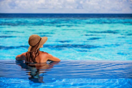 vacations: Having fun on beach resort, back side of sexy woman enjoying seascape from the pool, luxury summer vacation, travel and tourism concept Stock Photo