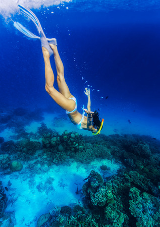 Woman diving to the sea bottom, watching for beautiful marine life, people activity on Maldives, summer adventure, extreme sport