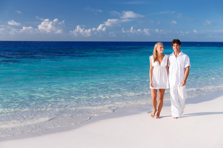Happy couple walking along beautiful sandy beach, young family holding hands and enjoying honeymoon vacation on Maldives photo