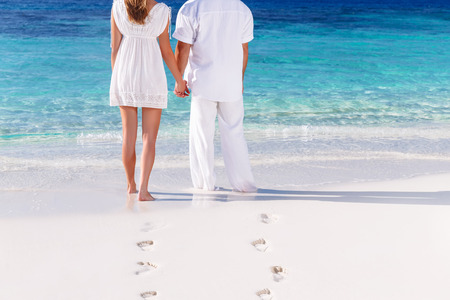 Back side of young couple standing on the white sandy beach and looking on the sea, body part, togetherness concept photo