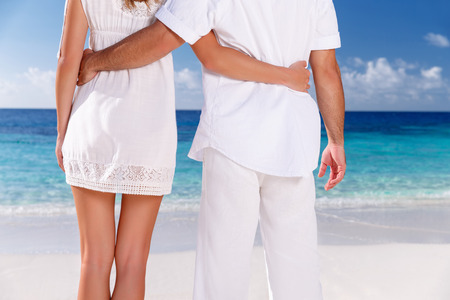 Closeup image of woman and man wearing white clothes enjoying seascape, body part, holding hands, summer vacation in love concept photo